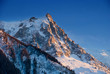 Aiguille du Midi mountain peak highlighted by sunset light.
