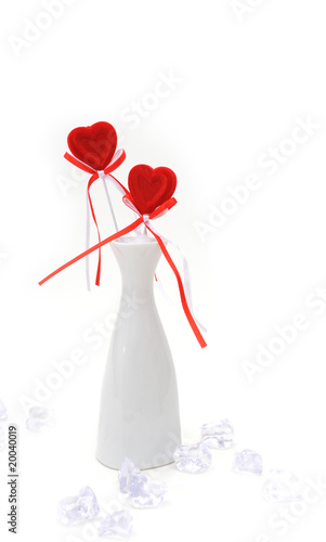 Two red plush hearts in white vase