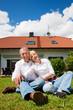 Älteres Paar sitzt vor ihrem Eigenheim