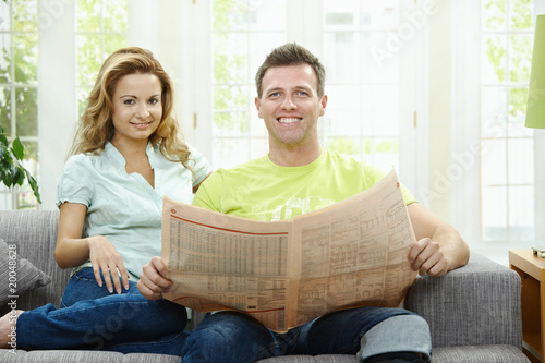 Happy couple reading news