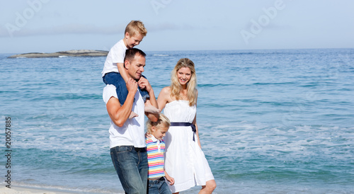 Lively family walking on the sand