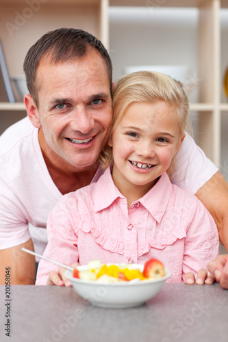Happy little girl eating fruit with her father