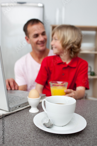 Jolly father and his son having breakfast