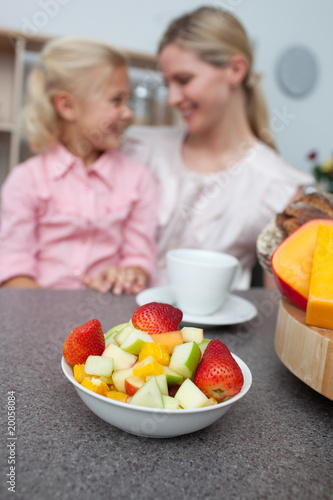 Blond little girl eating strawberry with her mother