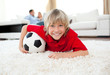 Smiling boy watching football match lying on the floor