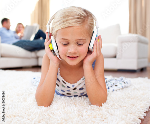 Cute little girl listening music lying on the floor