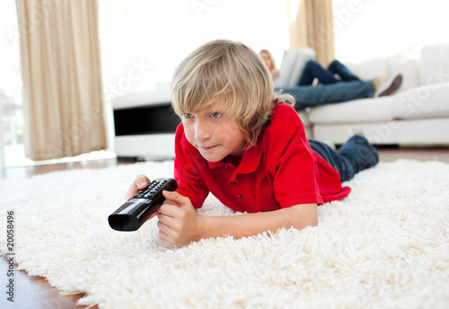 Cute boy holding a remote lying on the floor