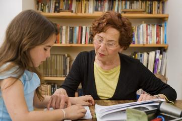 senior halping child doing homework