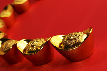 Traditional chinese gold ingots, red background, copy space
