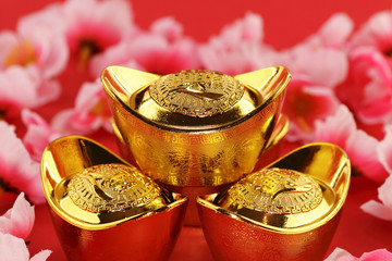 Chinese gold ingots with cherry blossoms on a red background