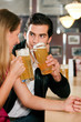 Couple in bar drinking beer flirting