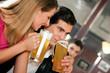 Paar in einer Bar trinkt Bier und flirtet