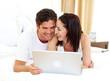 Enamoured couple using laptop
