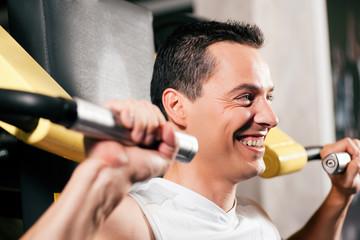 Mann trainiert am Gerät im Fitnessstudio
