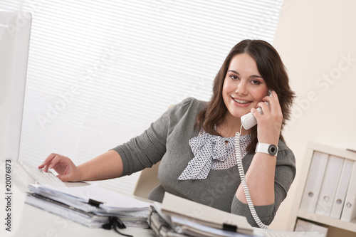 Smiling young woman on the phone at office