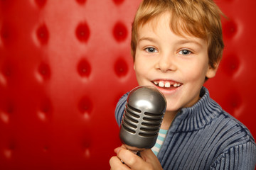 Singing boy with microphone on rack against red wall