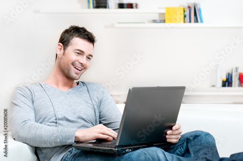 Smiling young man working on laptop