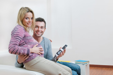 Smiling pregnant couple holding ultrasound scan