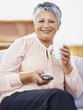 Senior woman holding TV remote while drinking coffee