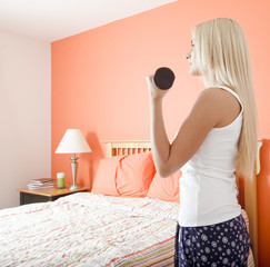 Woman Using Arm Weight in Bedroom