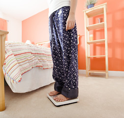 Woman Using Scale in Bedroom