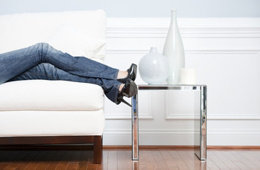 Woman's Leg's Reclining on White Couch