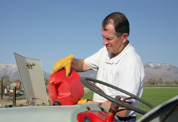 farmer gassing tractor