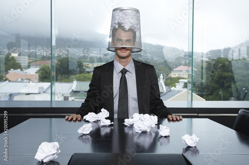 Businessman with a trash box on his head