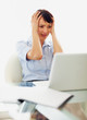 Tensed business woman holding her head in front of laptop