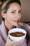 A mid adult woman eating a bowl of chocolate coated cereal