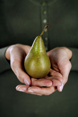 A woman holding a pear in her hands