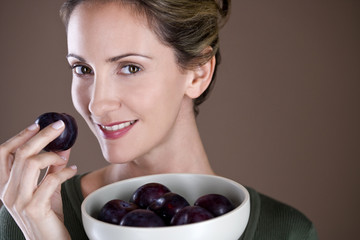 A mid adult woman eating a plum