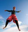 Jumping girl against the blue sky