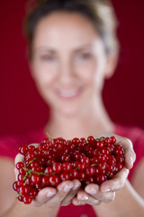 A mid adult woman holding a handful of redcurrants