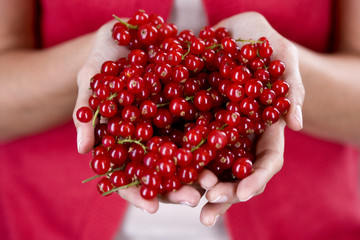 A woman holding a handful of redcurrants