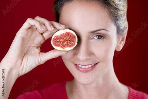 A mid adult woman holding half a fig in front of her eye