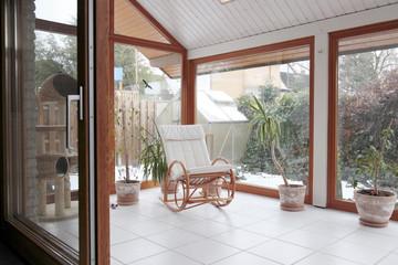 moderner Wintergarten mit Glasschiebetür und Schaukelstuhl