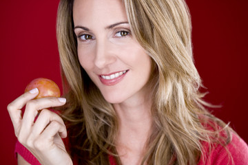 A mid adult woman holding a plum