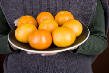 A woman holding a plate of clementines
