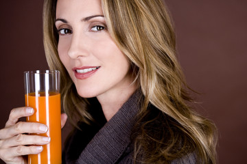 A mid adult woman holding a glass of fruit/carrot juice