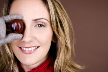 A mid adult woman holding a conker in front of her eye
