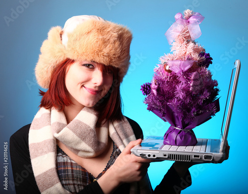 Girl with computer and xmas tree