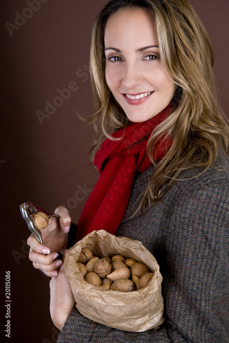 A mid adult woman cracking a nut