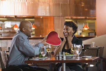 Man Giving Woman Heart Shaped Box at Restaurant