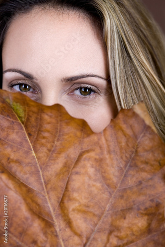 A mid adult woman looking over a dried leaf