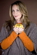 A mid adult woman holding a small pumpkin