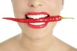 Beautiful woman teeth eating red pepper