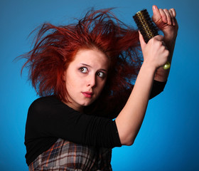 Girl with hair raiser in panic try to combing own hair