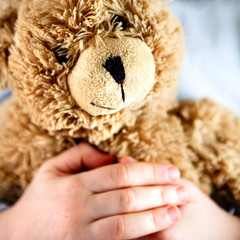 Old Teddy Bear in the Hands of a Child