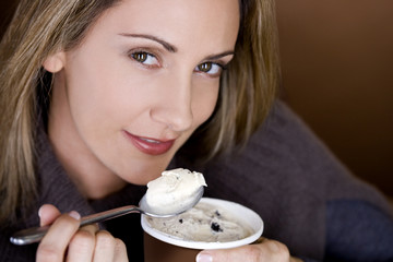 A mid adult woman eating ice cream, close-up